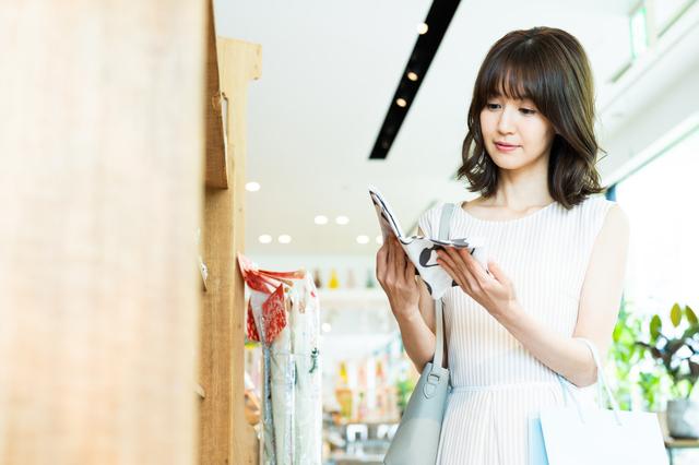 スマホを見ながら買い物する女性
